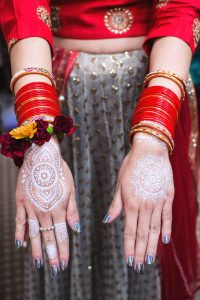 Woman Wearing Red Dress Showing Her Henna Tattoos